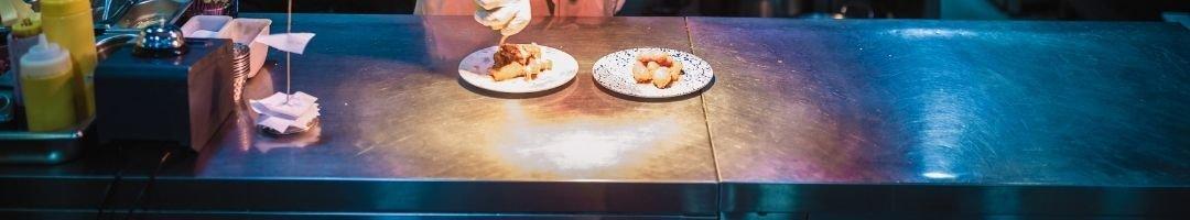Speisen werden auf Arbeitstisch vorbereitet.