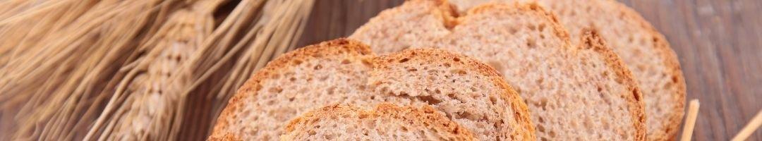 Brotscheiben mit Weizen im Hintergrund