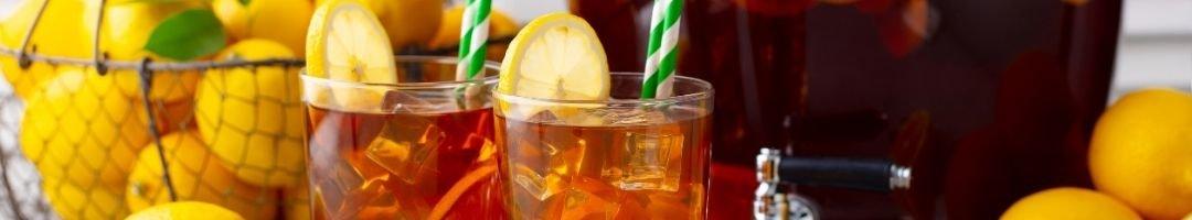 Gläser mit Lemonade, Eiswürfel, Zitrone und Strohhalme
