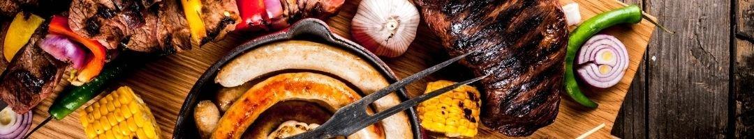 Pfanne mit Würstchen und Fleisch auf einem Holzbrett