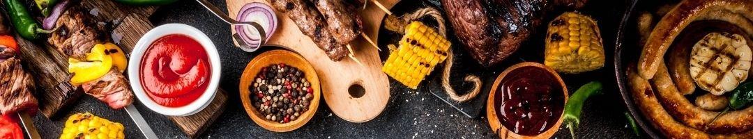 Holzbretter mit Fleischspieße, Saucen, Gewürzen und...