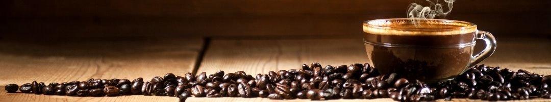 Glastasse mit Kaffee und Kaffeebohnen drumherum