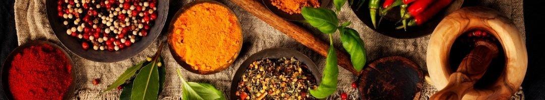 Schalen mit Pfeffer, Paprikapulver, Currypulver und Pulver