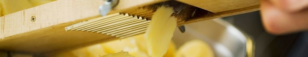 Holzmandoline die Kartoffel in Scheiben reibt