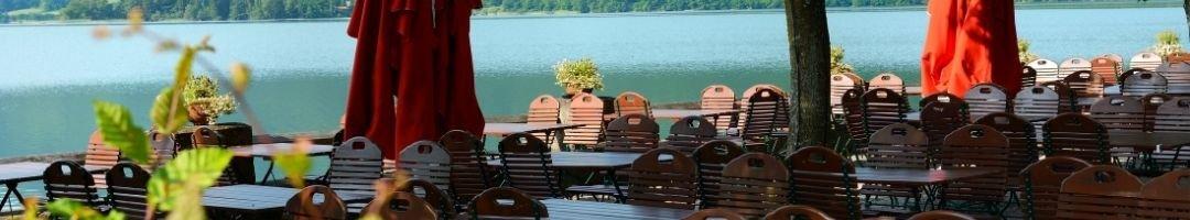 Biergarten am Wasser mit Tische, Stühle und Sonnenschirme
