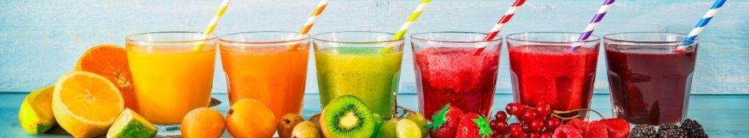 Saftgläser mit Früchten und Strohhalme