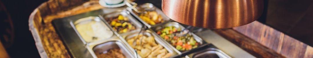 Warmhaltelampe über eine Buffetinsel mit Speisen